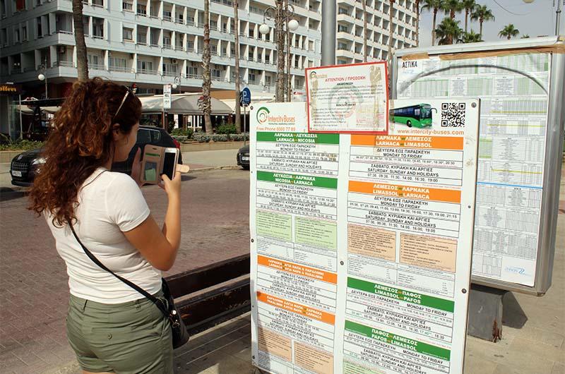 Туристка изучает расписание автобусов из города Ларнака до своего курорта.